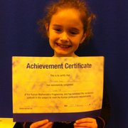 Student at the Solihull Tudor Grange Kumon Tuition Centre receiving her achievement certificate in maths