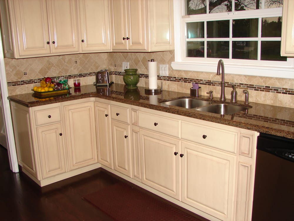 Antique white raised panel cabinets and tropical brown for Brown kitchen cabinets with black granite