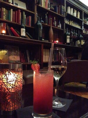 An old library with books still intact transformed into a cute bar to the left of the restaurant while you wait for your table.