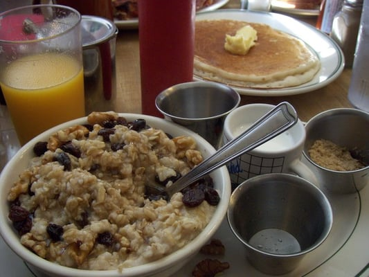 Pantry Family Restaurant - Oatmeal with brown sugar, walnuts, and raisins. Hotcake in background. - San Mateo, CA, Vereinigte Staaten