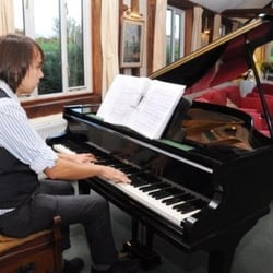 A wedding pianist playing the piano for…
