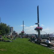 Victor Steinbrueck Park - Seattle, WA, États-Unis. Two totem poles tower above and people lie below.