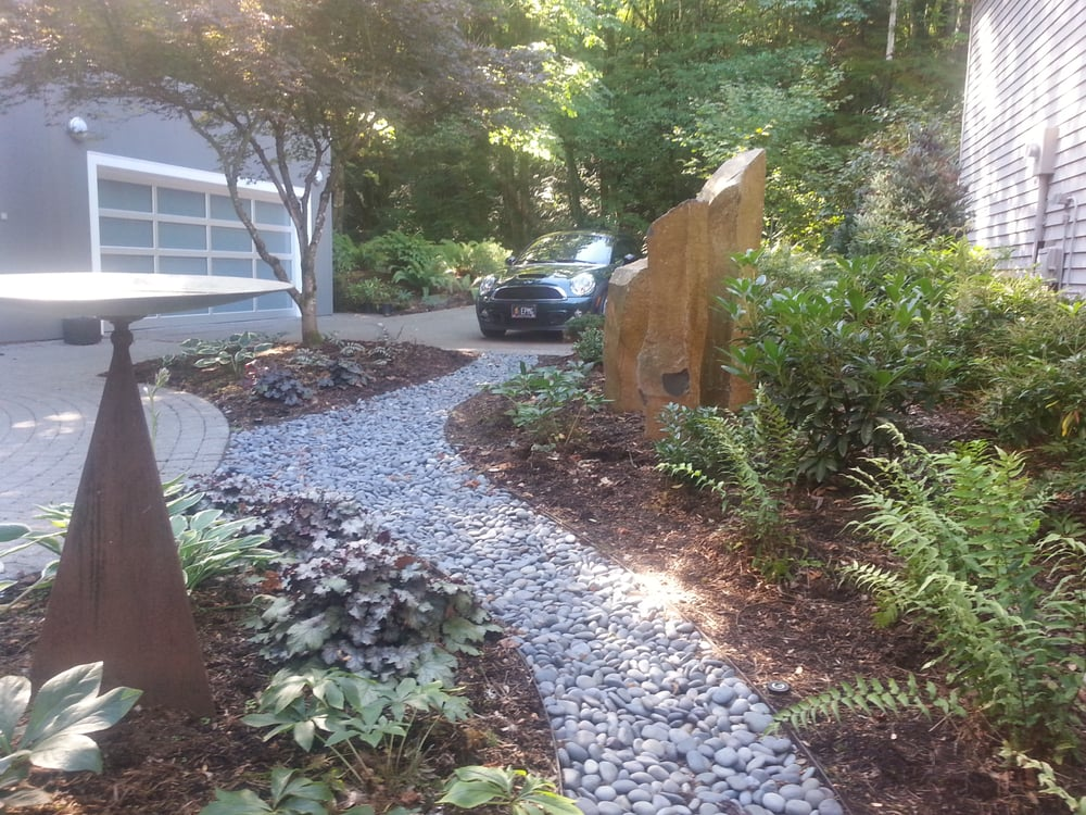 The river stone path gives structure to the narrow front ...
