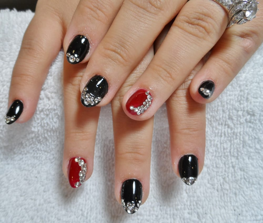 , CA, United States. Black & red gel nails with rhinestones design