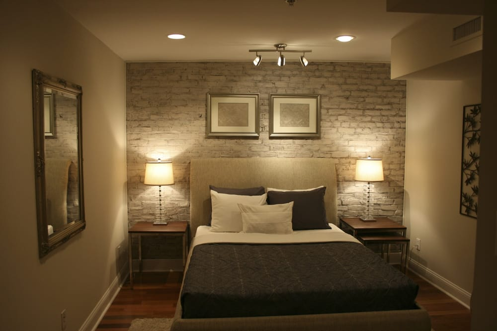 staged bedroom in condo exposed brick wall painted and