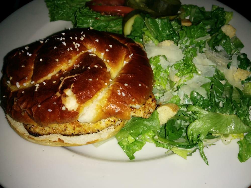 Blackened chicken sandwich on a pretzel bun with Caesar salad. | Yelp