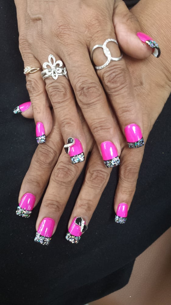 Acrylic nails with pink polish on nail bed, black polish as base on ...