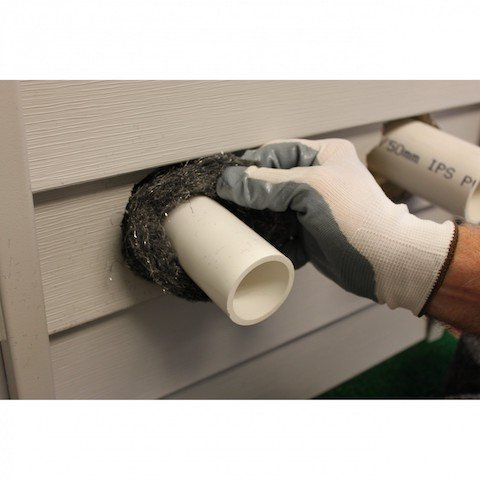 Sealing hole around pipe with steel wool to prevent rodents