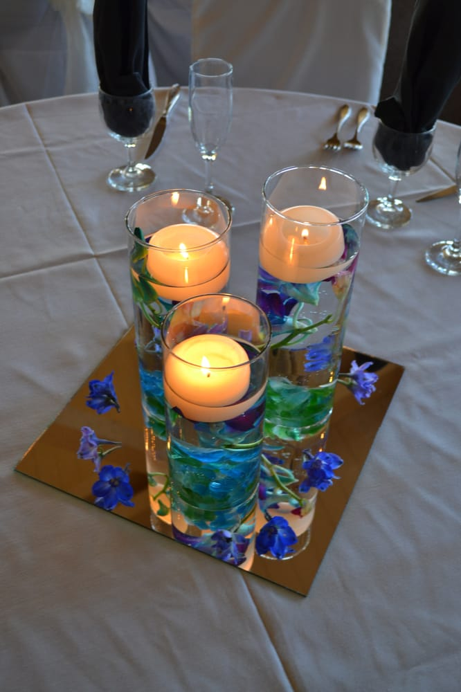 Peacock colors in a submerged centerpiece with candle