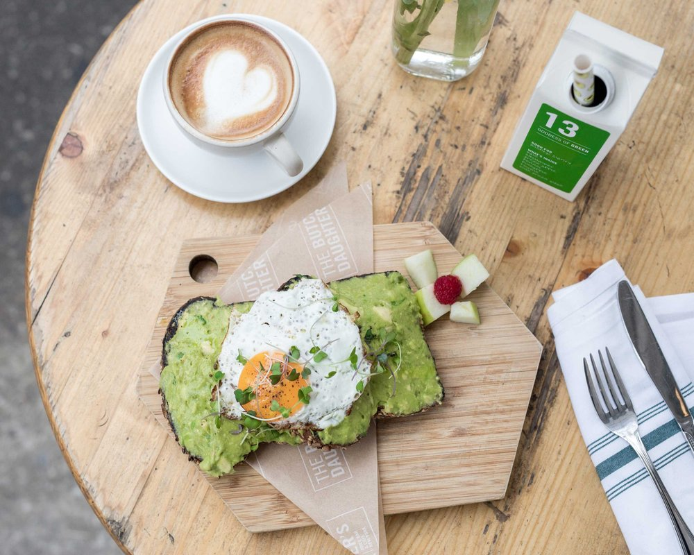 Photo of The Butcher's Daughter - New York, NY, United States. The double smashed avocado toast with a sunny side up egg on top.