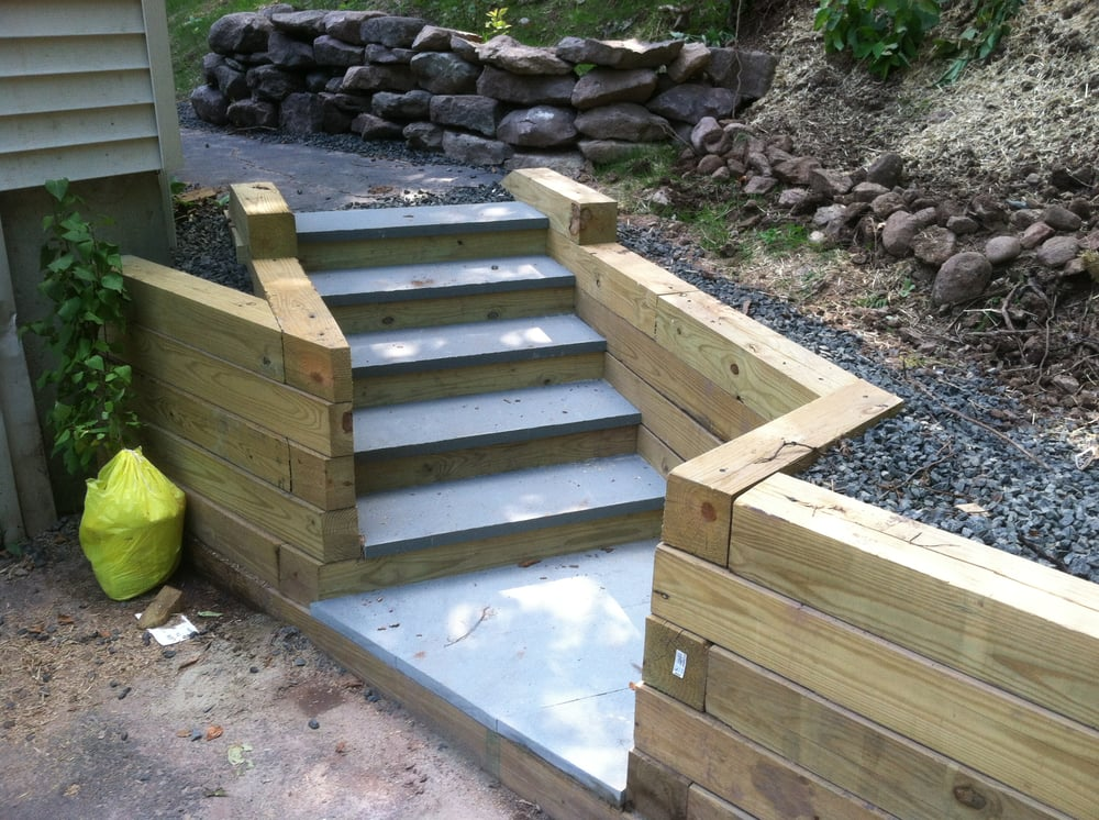 Bluestone capped timber steps add character to this new for Landscape drainage