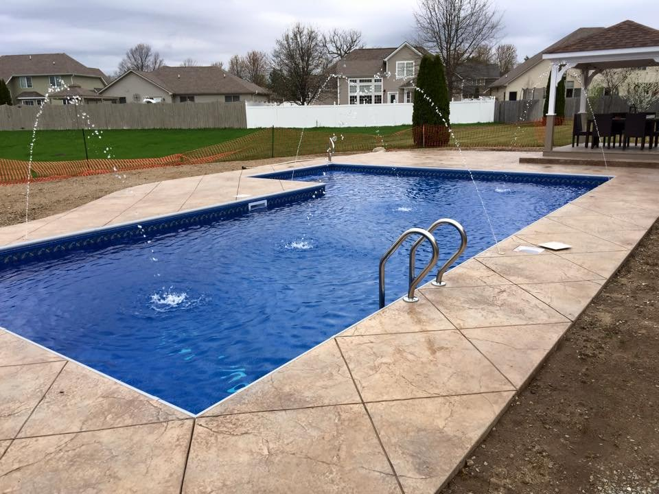 L-shaped inground swimming pool with deck jets and stamped ...