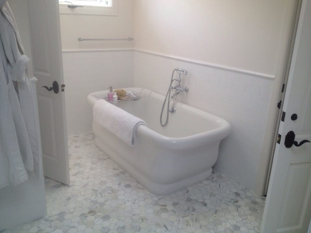 White hexagon marble floor with 3 x6 subway tile capped with chairail master bathroom in la Marble hex tile bathroom floor