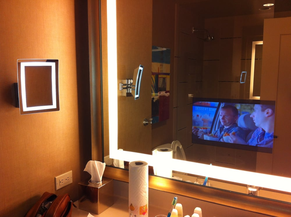 tv monitor in bathroom mirror, with lighted magnified mirror on