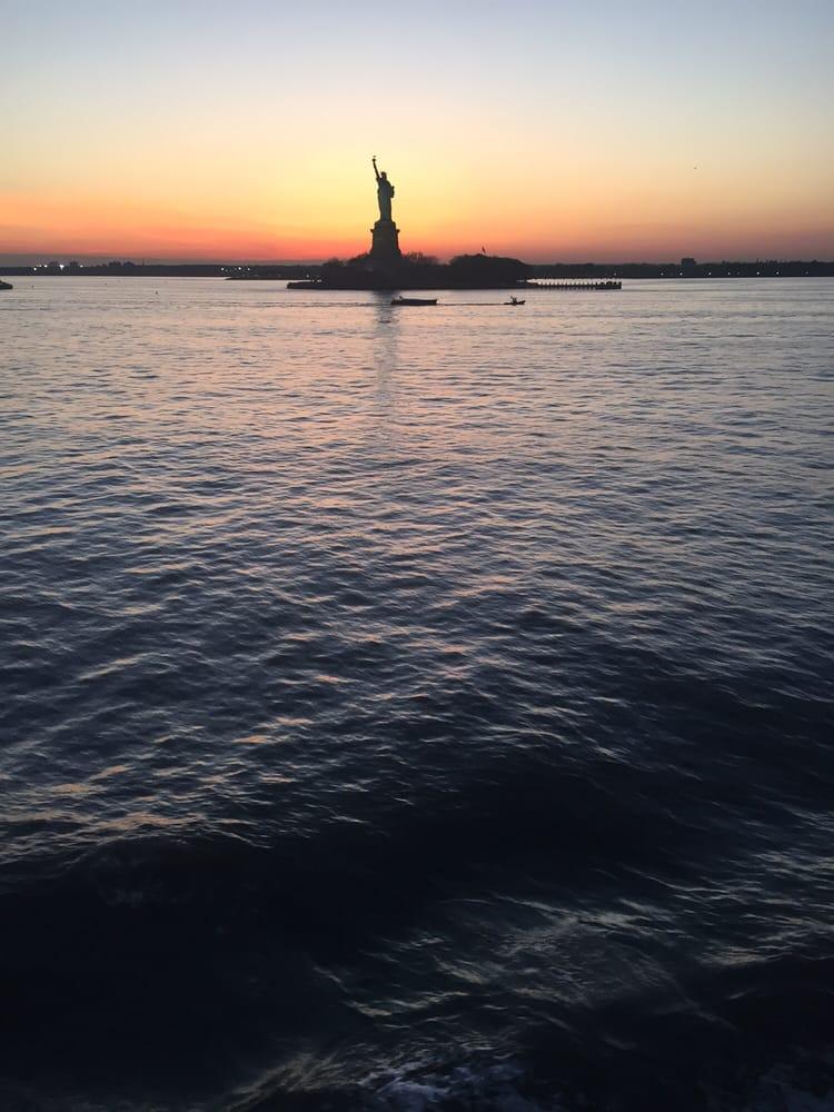 Photo of The Staten Island Ferry - Staten Island, NY, United States. Lady liberty and a beautiful sunset