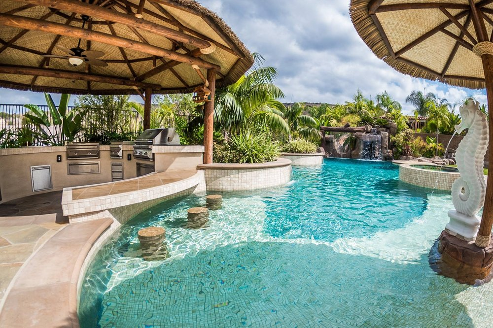 Tropical beach entry custom swimming pool with a perimeter ...