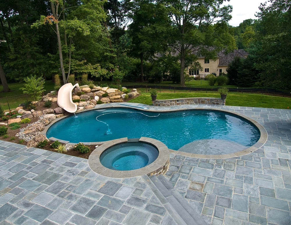Pool sun shelf raised spa landscape slide with boulder for Raised swimming pool designs