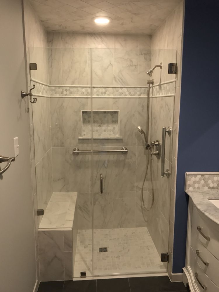 A Walk in shower with frameless glass enclosure, tile bench seat and ...