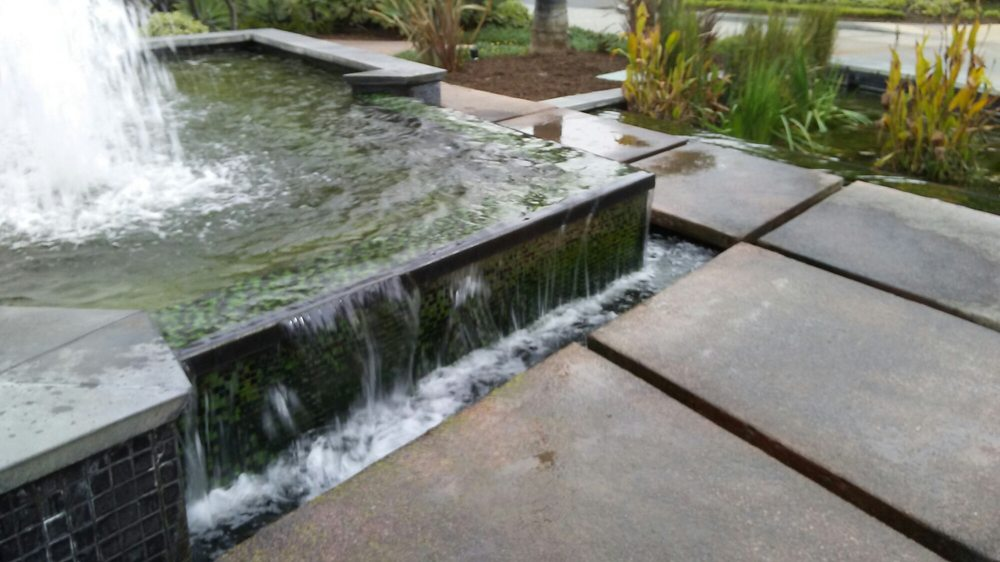 Infinity waterfall flowing down between stepping stones into