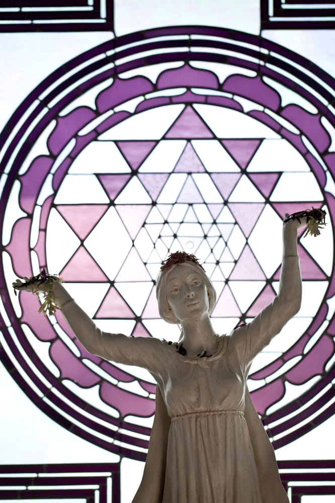 A Blessed Mother statue with a Sri Yantra stained glass