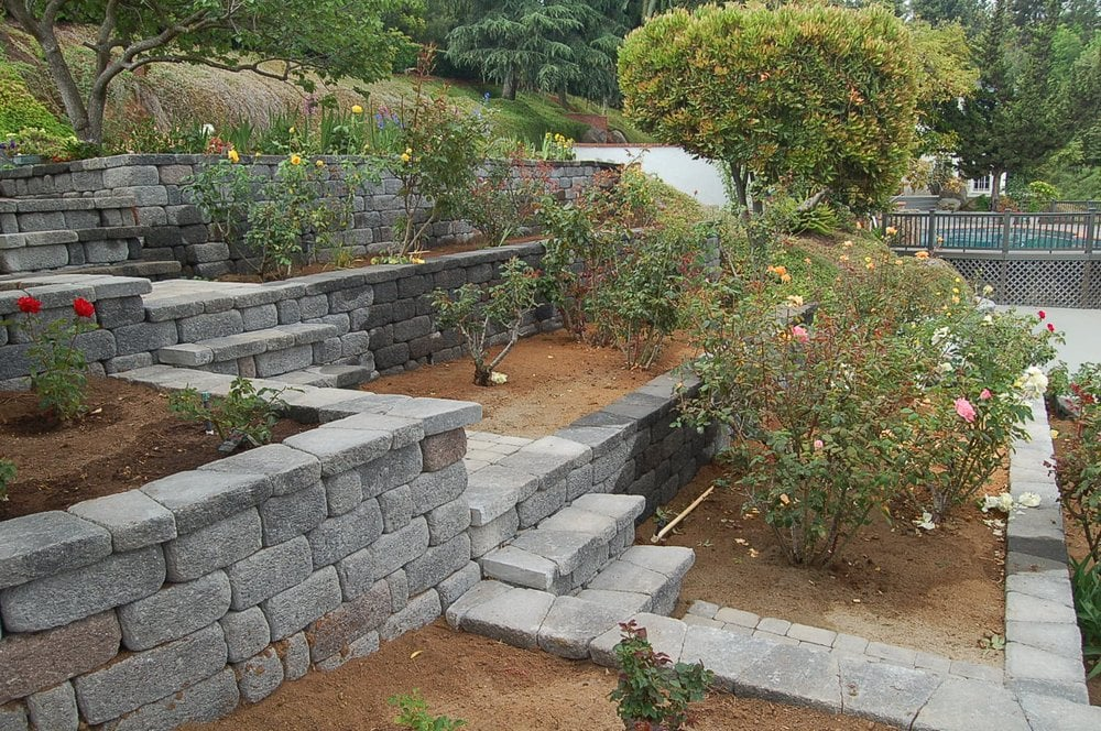 Terraced hillside garden with stone work and patio by east - How to terrace a hillside ...