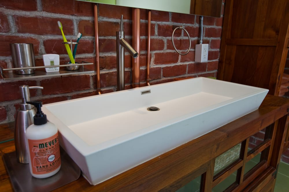 sink installed in a basement bathroom exposed copper piping adds to