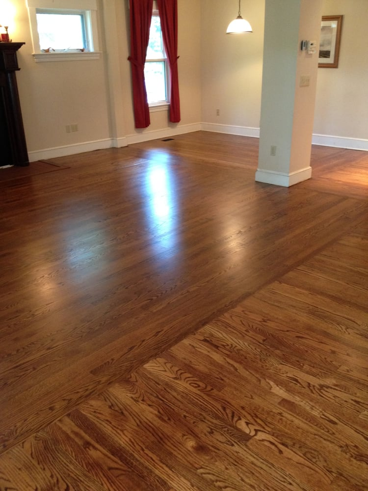 A stained oak floor that is located in a open layout for Opposite of floor