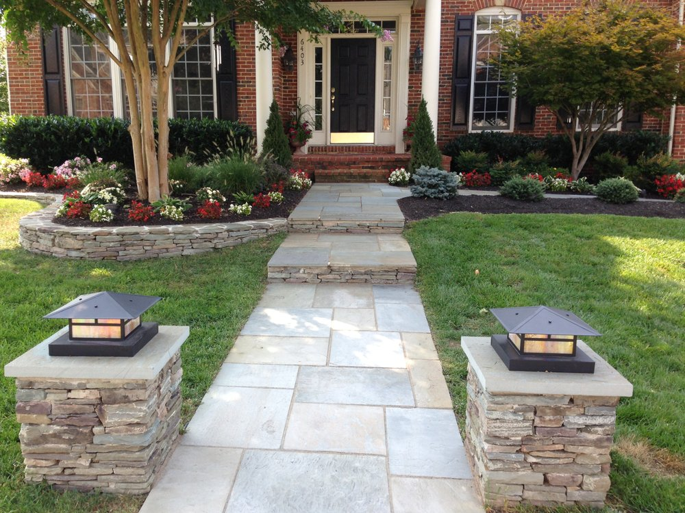 lighted stacked stone columns square cut flagstone walkway set in