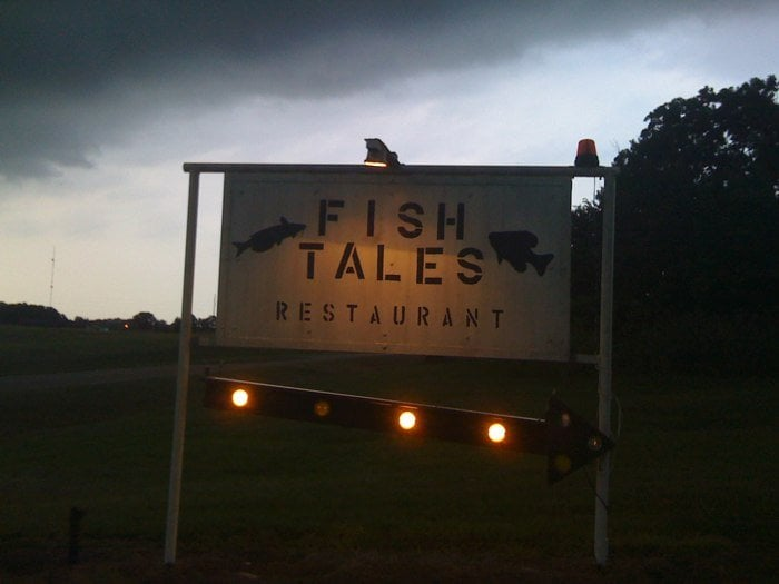 The sign at dusk yelp for Fish tales restaurant